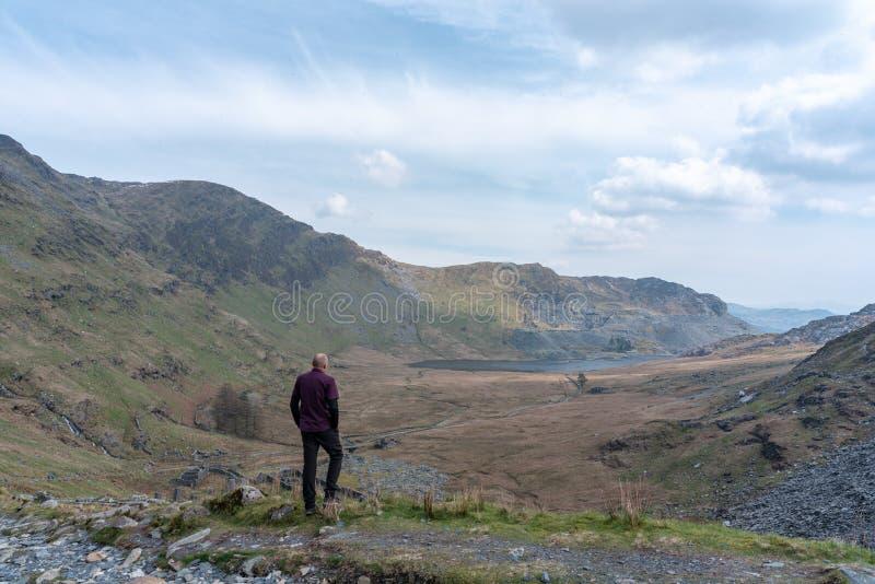 Plas Cwmorthin, Terrace and Rhosydd Slate Quarry, Blaenau Ffestiniog. A walker enjoying the view of Plas Cwmorthin, Terrace and Rhosydd Slate Quarry at Blaenau stock photo