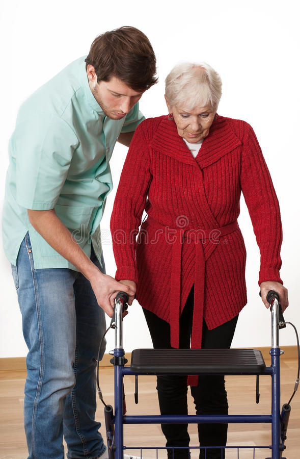 Walker lesson. Nurse teaching elder disabled person how to walk with walker stock photography