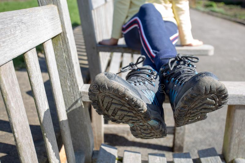 Walking boots muddy resting after walk ramble sitting on bench. Walker resting after ramble sitting on wooden bench with muddy walking boots sunny day resting royalty free stock photography