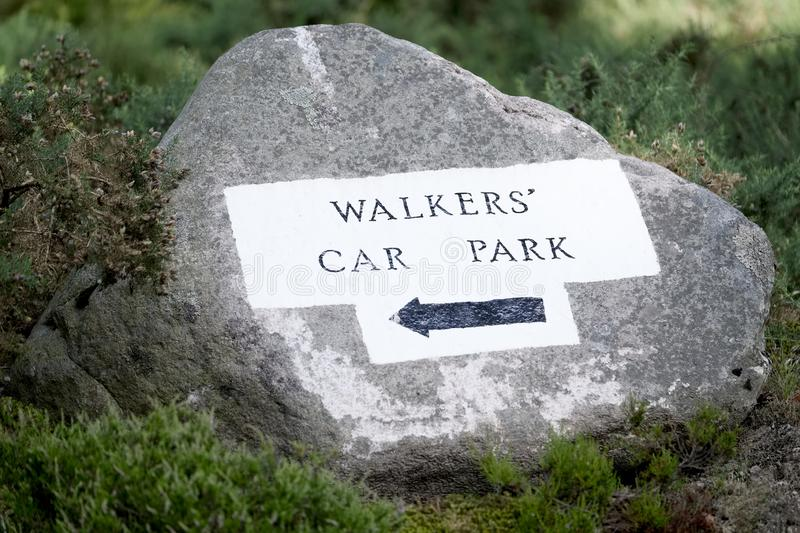 Walkers car park direction arrow sign painted on rock in woodlands. Uk stock photos