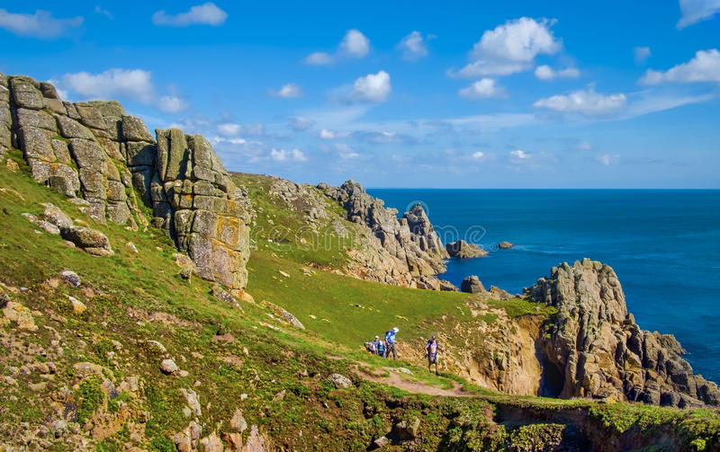 Walkers, Cornwall Coastal Path, England. Walkers along the dramatic Coastal Path in Cornwall, Great Britain, with rugged cliffs and very blue ocean, on the way stock images