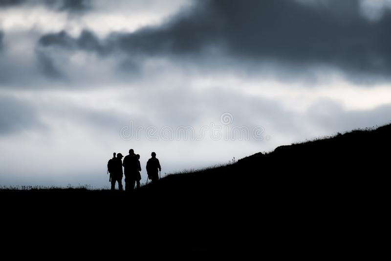 Walkers on Handa Island. Silhouetted against a moody dramatic sky stock photo