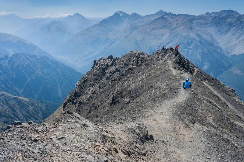 Walkers on peak in Southern Alps. New Zealand stock image