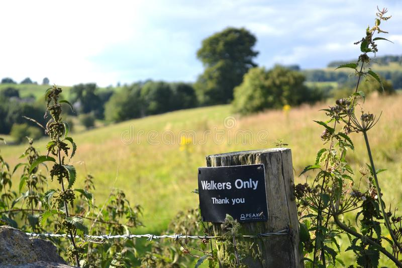 Walkers Only Sign In Sunny Landscape. Tourist sign in fields in the Peak District, England, UK; with blue sky, clouds and trees in the background and flowers/ royalty free stock image