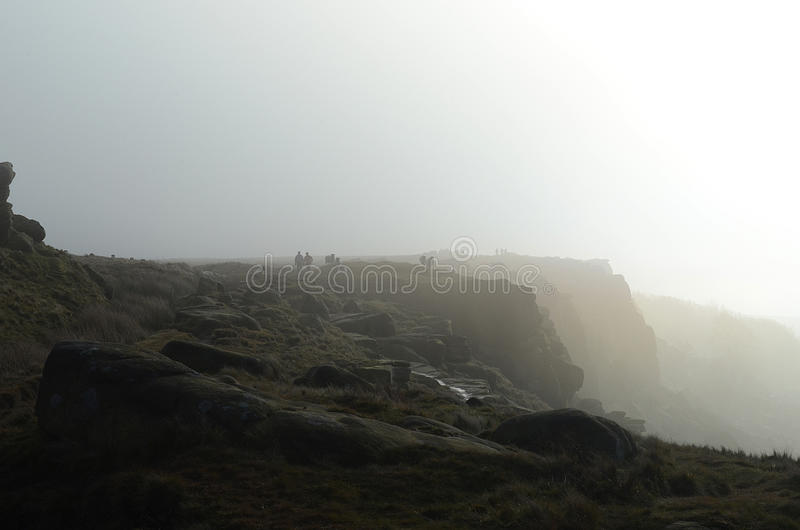 Walkers on Stanage Edge. Stanage edge in the mist, Hathersage, Derbyshire stock photos