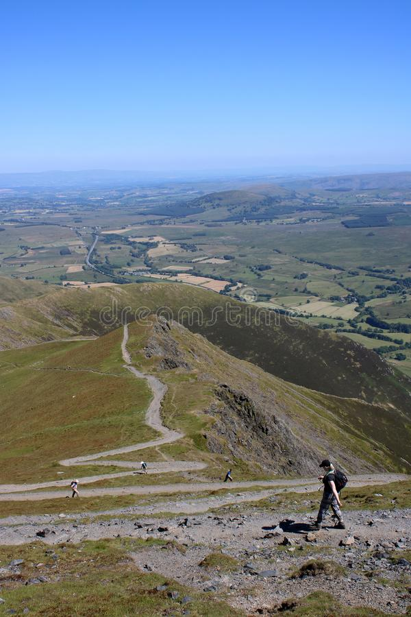 Walkers on zig-zag path on Blencathra, Cumbria, England. Walkers on footpath with zig zags descending and ascending Blencathra Saddleback towards Scales Fell in stock image