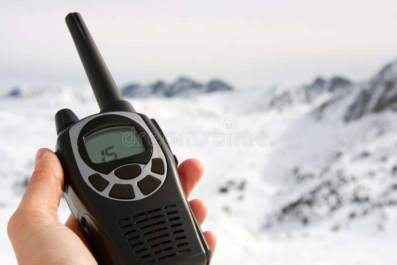 Walkie talkie. Black walkie talkie in a hand, mountains on the background stock photo