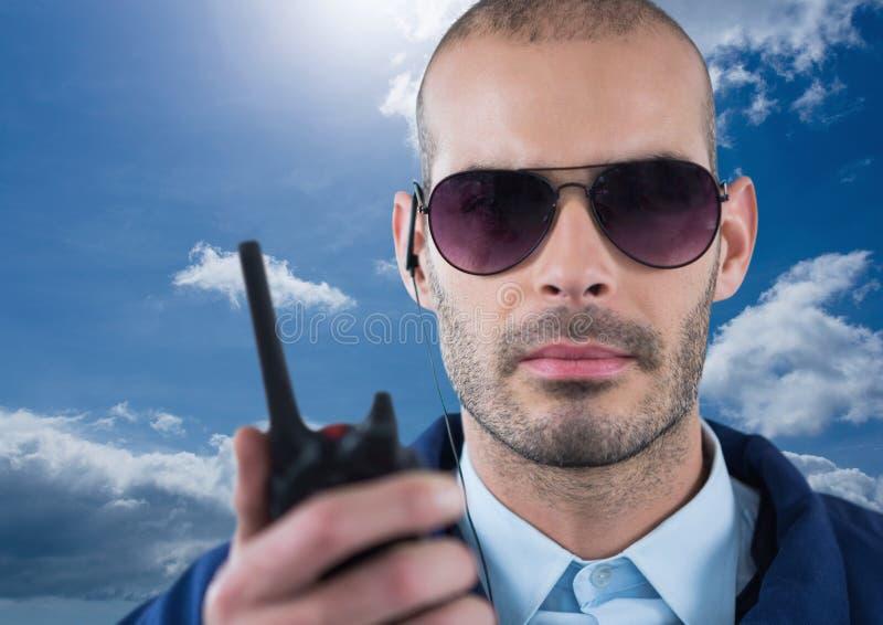 Walkie-talkie della tenuta della guardia giurata durante il giorno soleggiato immagini stock libere da diritti