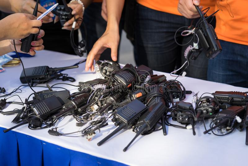 Walkie-talkie portatili sulla tavola con le mani dell'uomo immagine stock