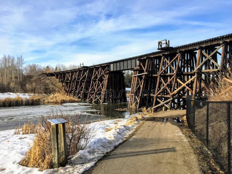 Walking along a pathway beside the Sturgeon River in St. Albert, Alberta, Canada. The snow and ice are melting and there is an old wooden train bridge in the royalty free stock photography