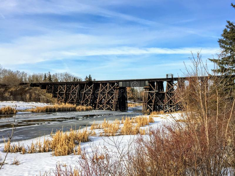 Walking along a pathway beside the Sturgeon River in St. Albert, Alberta, Canada. The snow and ice are melting and there is an old wooden train bridge in the royalty free stock image