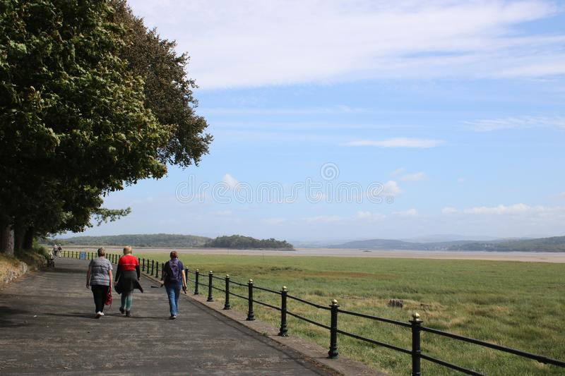 Walking along promenade Grange-over-Sands, Cumbria. Three people walking along the promenade at Grange-over-Sands, Cumbria, England near to the site of the stock images