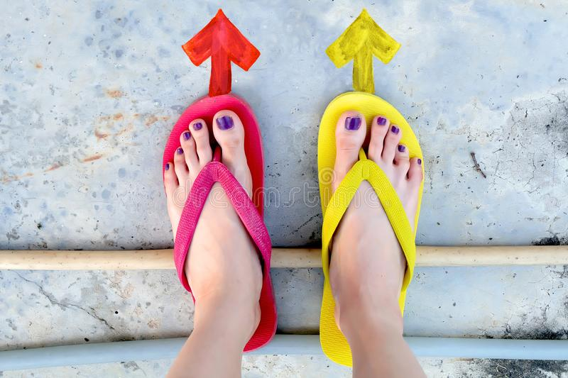 Walking Arrows Directions Drawn. Woman Wear Flip Flop Red and Yellow Standing on Cement Background stock images