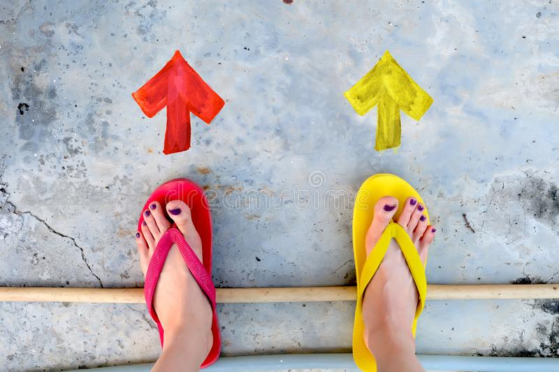 Walking Arrows Directions Drawn. Woman Wear Flip Flop Red and Yellow Standing on Cement Background stock photography
