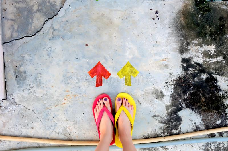 Walking Arrows Directions Drawn. Woman Wear Flip Flop Red and Yellow Standing on Cement Background royalty free stock photography