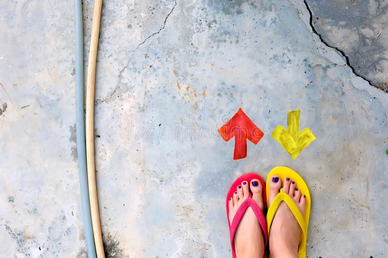 Walking Arrows Directions Drawn. Woman Wear Flip Flop Red and Yellow Standing on Cement Background. Great for Any Use stock image