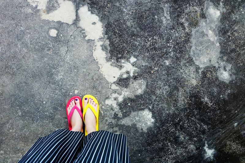 Walking Arrows Directions Drawn. Woman Wear Flip Flop Red and Yellow Standing on Cement Background royalty free stock photo