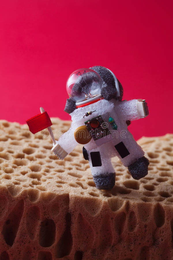 Walking astronaut, red background. Light bulb character dressed in spacesuit and spaceman ammunition. Cosmonaut with stock photos