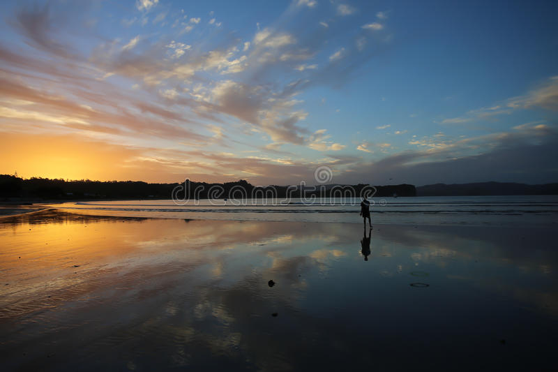 Walking on the beach at sunset stock photography