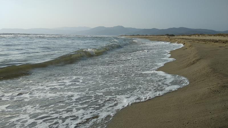 Walking on the beach among the waves royalty free stock photography