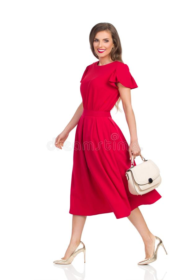 Walking Beautiful Woman In Red Dress, Gold High Heels And Beige Purse. Beautiful young woman in red dress and gold high heels is holding beige purse, looking at stock photo