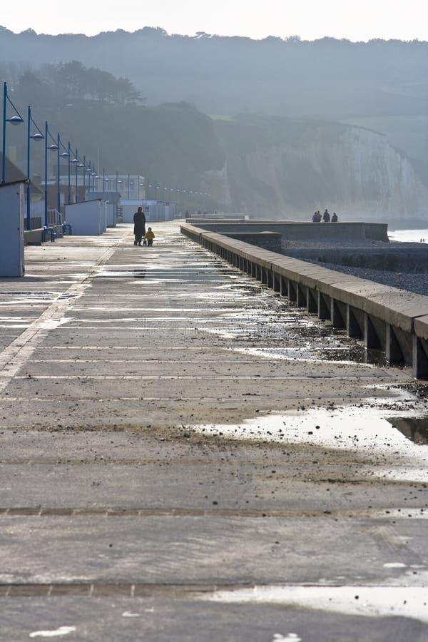 Walking on the boardwalk. People walking on the boardwalk along the Normandy Coast royalty free stock photography