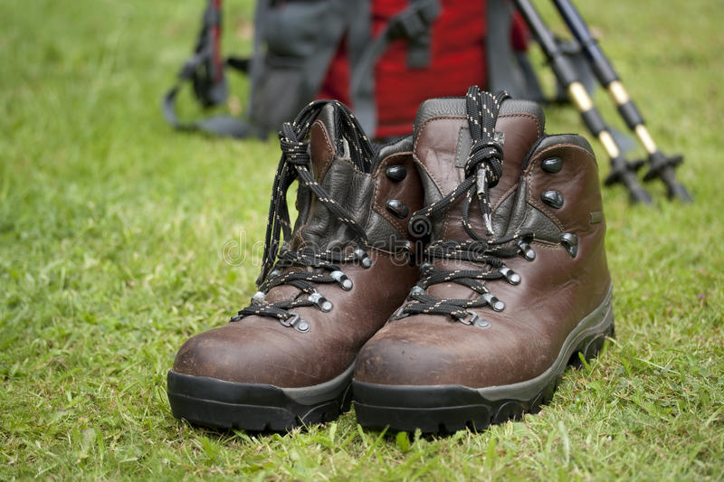 Walking boots. A pair of old worn brown walking boots and red day pack stock photos