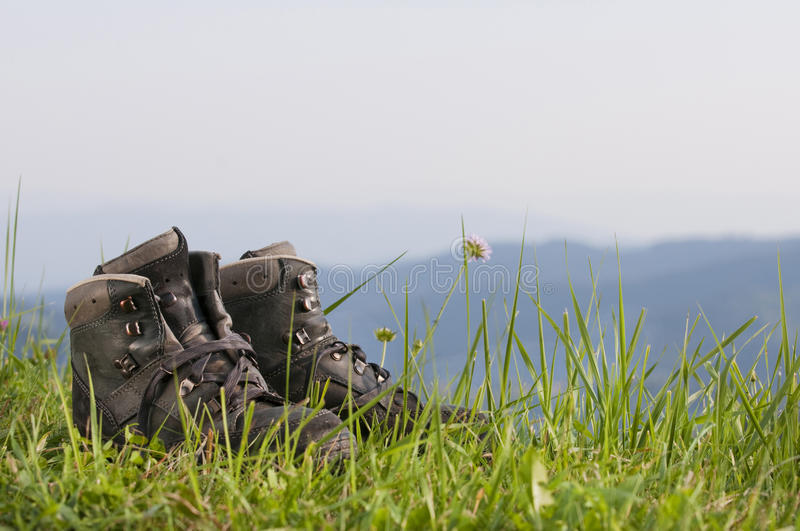 Walking boots. On meadow in landscape royalty free stock image