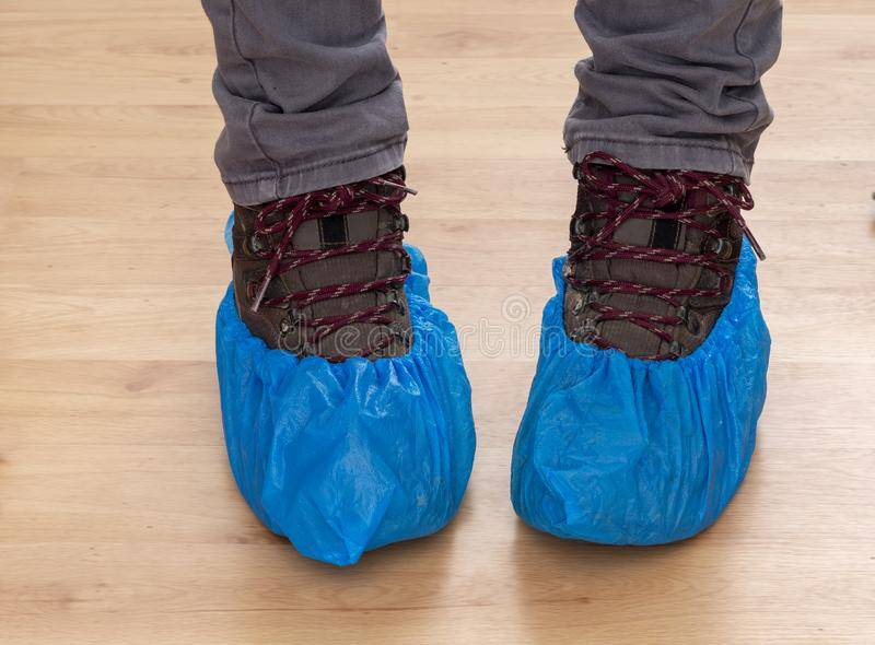 Walking boots and feet in blue plastic shoe protectors, covers. Hygiene in medical situations etc. Single use. Walking boots and feet in blue plastic shoe stock photography