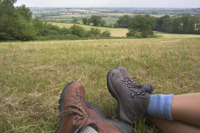 Walking boots. Man and womans walking boots in the foreground of a countryside view royalty free stock images