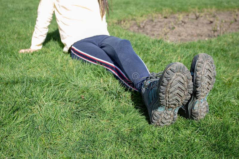 Walking boots muddy resting after walk ramble sitting on bench. Walker resting after ramble sitting on wooden bench with muddy walking boots sunny day resting stock photo