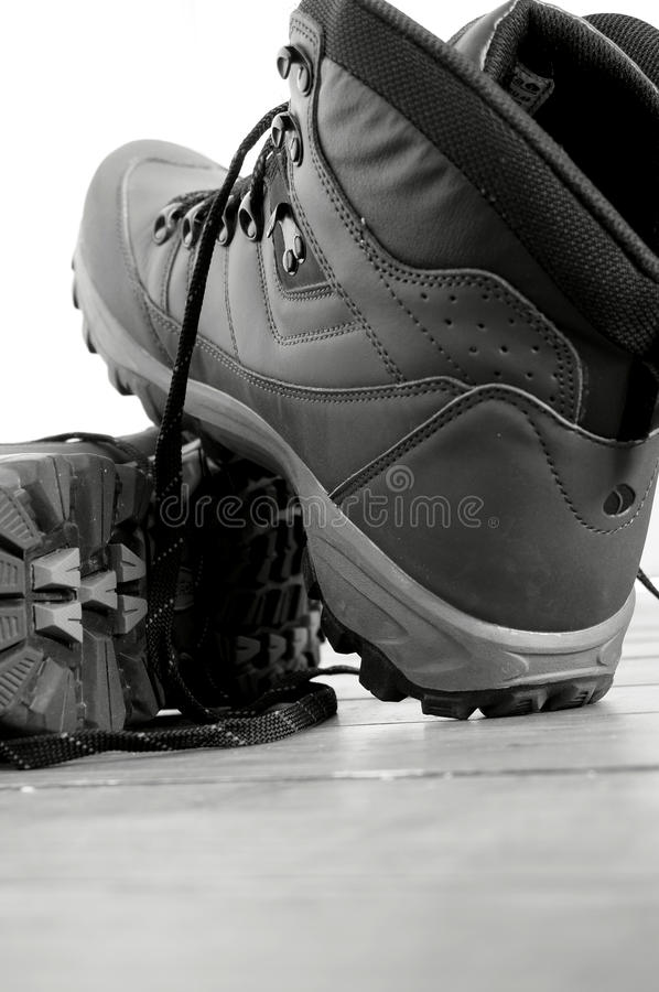 Walking boots A. Photograph of a pair of walking boots on a wooden floor in black and white royalty free stock photos