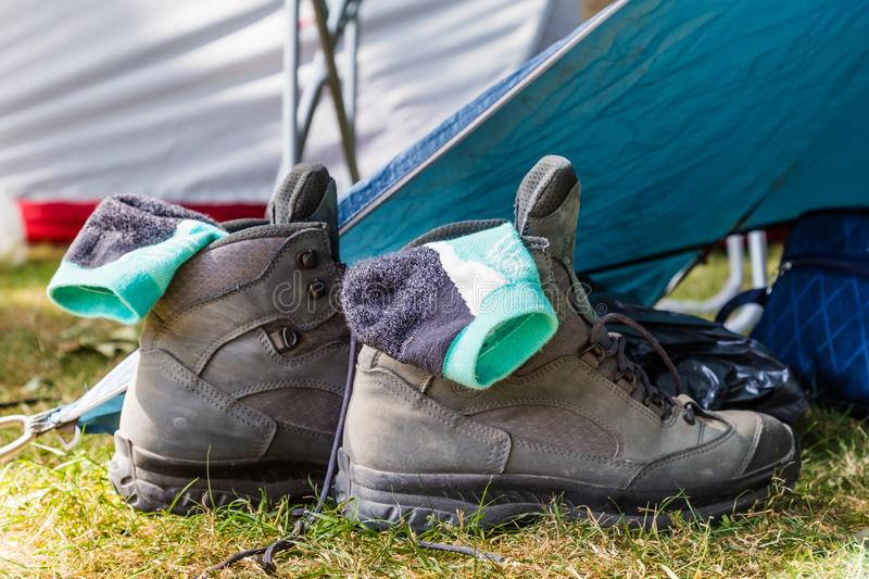 Walking boots beside a tent. Walking boots with socks beside a tent on a campsite royalty free stock photos