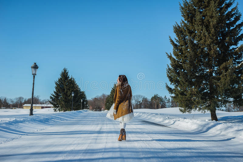 Walking bride on a snowy road. beautiful brunette in a short wedding dress, rustic style, with the pine-tree wedding bouquet, and royalty free stock photography