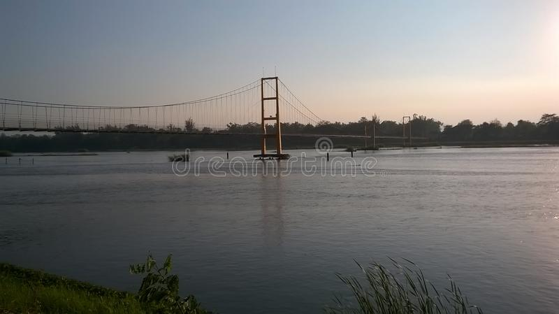 Walking bridge over a river at sunset. royalty free stock photography