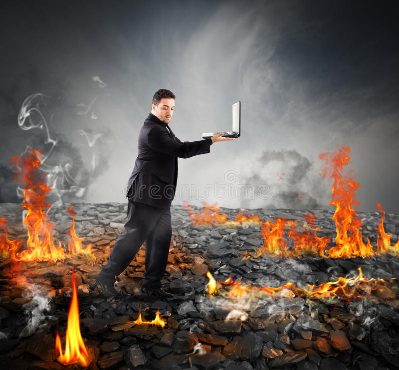 Walking on burning charcoal. Businessman with pc walking on burning charcoal stock photography