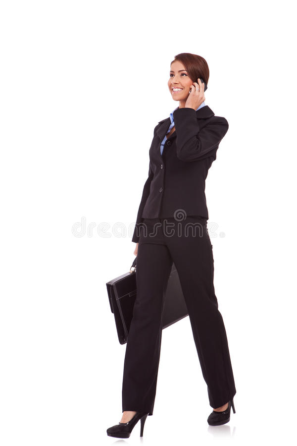 Walking business woman on the phone royalty free stock photo