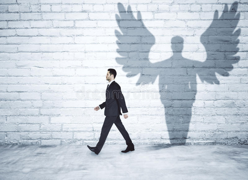 Walking businessman with angel shadow stock image