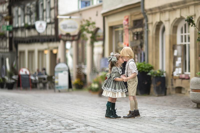 Walking children on the street.The relationship of a girl and a boy . Photos in retro style . Pavers in the city center.Summer. Germany royalty free stock images
