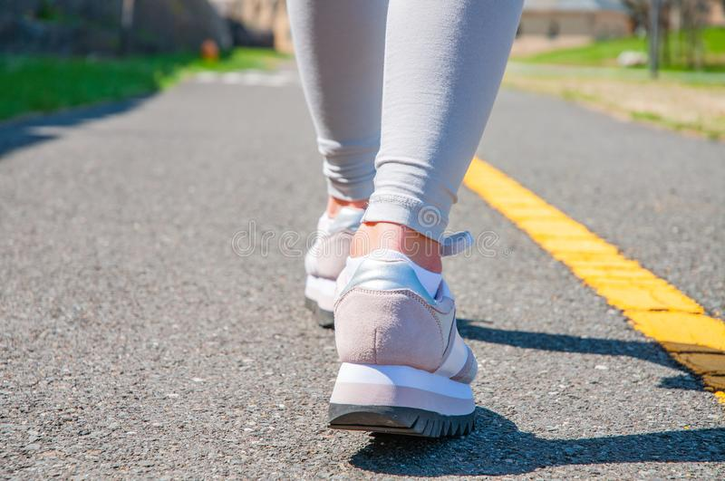 Walking. Close-up of women`s running shoes on a paved trail. stock photo