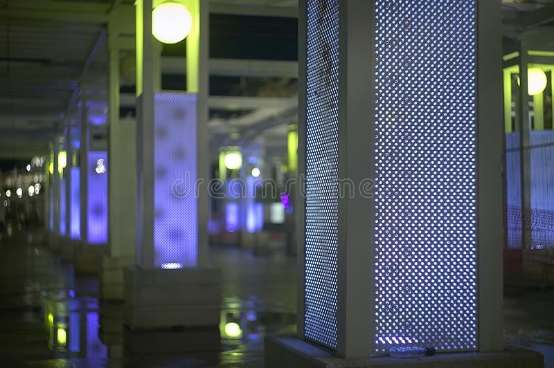 Moment of solitary reflection in the night. Walking with columns illuminated by blue lights without anyone passing or stopping, a solitary example of walking in stock photos