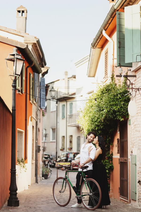 Walking a couple of lovers in the streets of the old city, with a bicycle. The woman gently hugs her man stock photo
