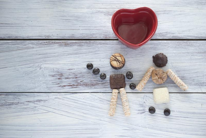 Walking couple made with chocolate cookies. Heart shape ceramic. Concept of friendship, love, marriage, honeymoon, party royalty free stock images
