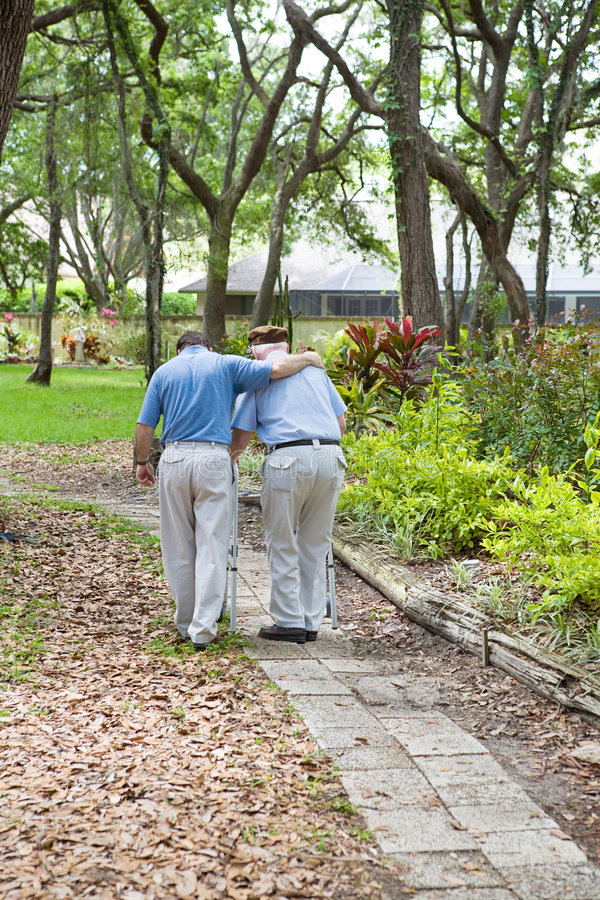 Walking With Dad. Adult son walking his senior grandfather in the park. Vertical view with room for text