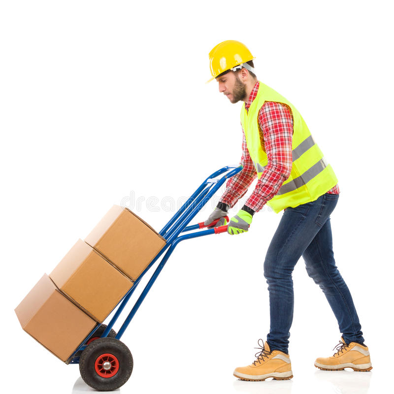 Walking delivery man. Serious man in yellow hardhat and lime reflective vest pushing a delivery cart. Full length studio shot isolated on white stock image
