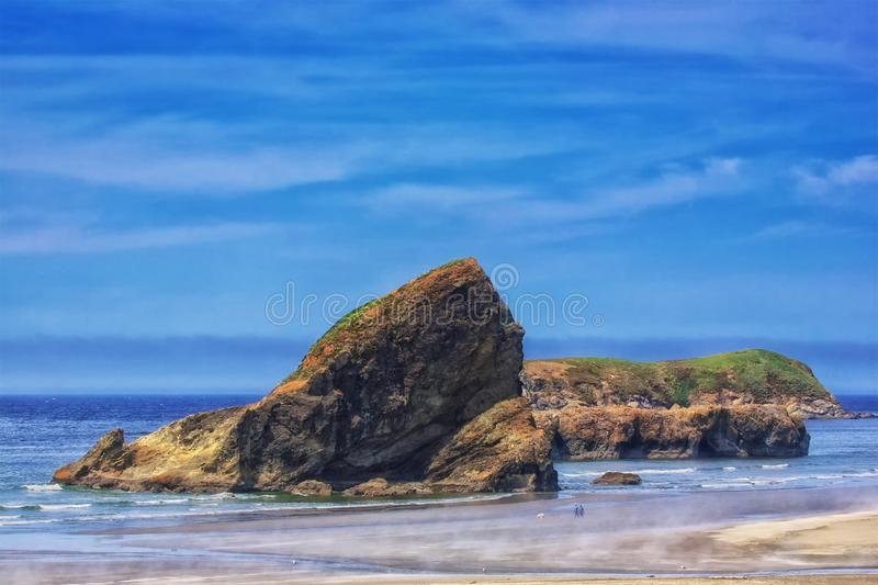 Walking the dog on a Fall day at the beach as steam rises from the warming sand. The rugged west coast of Oregon, USA has spectacular views and beaches. Ariya`s stock photo