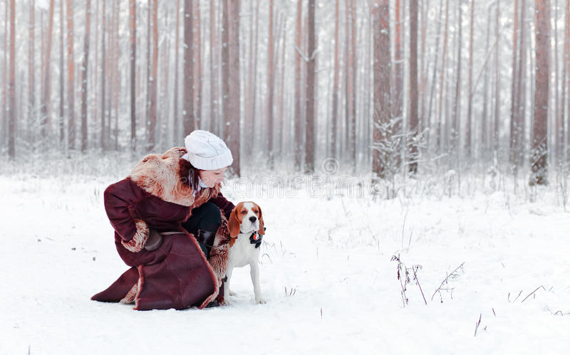 Walking with dog. Woman walk with dog in snowy forest royalty free stock photography