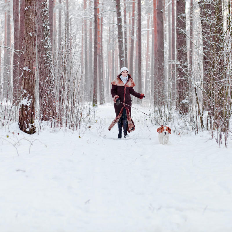 Walking with dog. Woman walk with dog in snowy forest royalty free stock photos