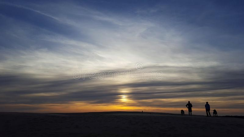Walking dogs on sand dunes in the Outer Banks, North Carolina royalty free stock photo