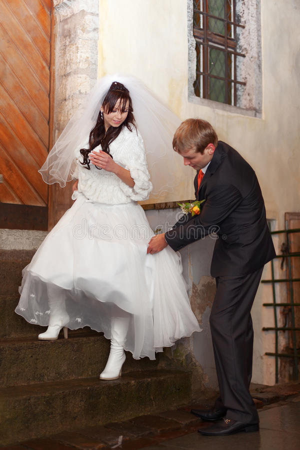 Walking down. Groom is helping bride getting down and stay clean. Focus on bride stock photo